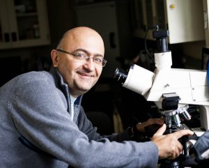 Alfonso Abizaid next to a microscope
