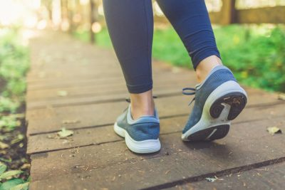 Image of a close up of female legs with running shoes on wooden footpath in woods. Nature and sport healthy lifestyle concept.