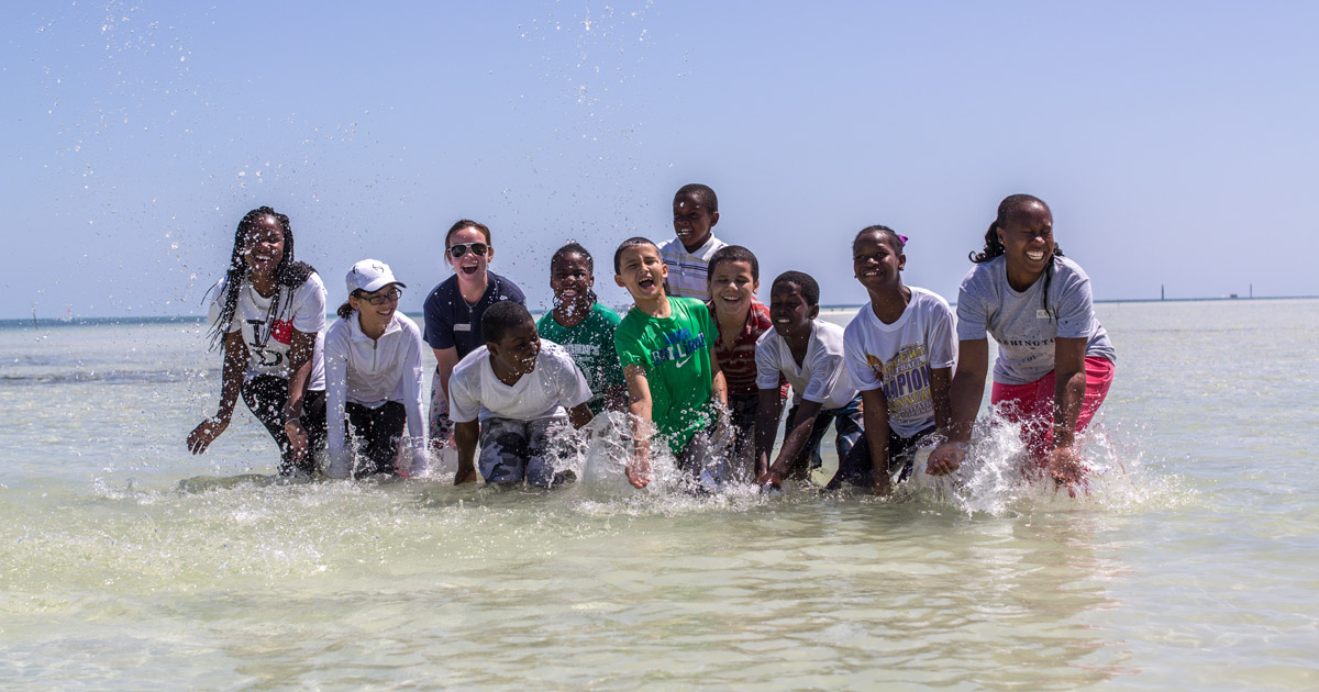 Jill Brooks in the ocean splashing with school students